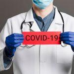 médico com uma placa que diz covid-19