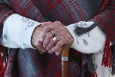 Pormenor de idosa com mãos sobre a bengala