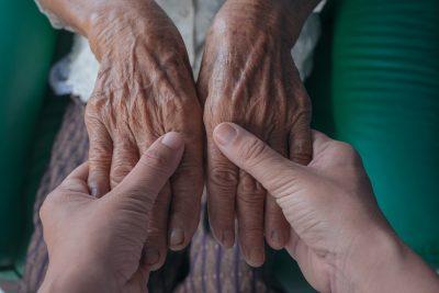 Jovem segura mãos de uma pessoa de idade