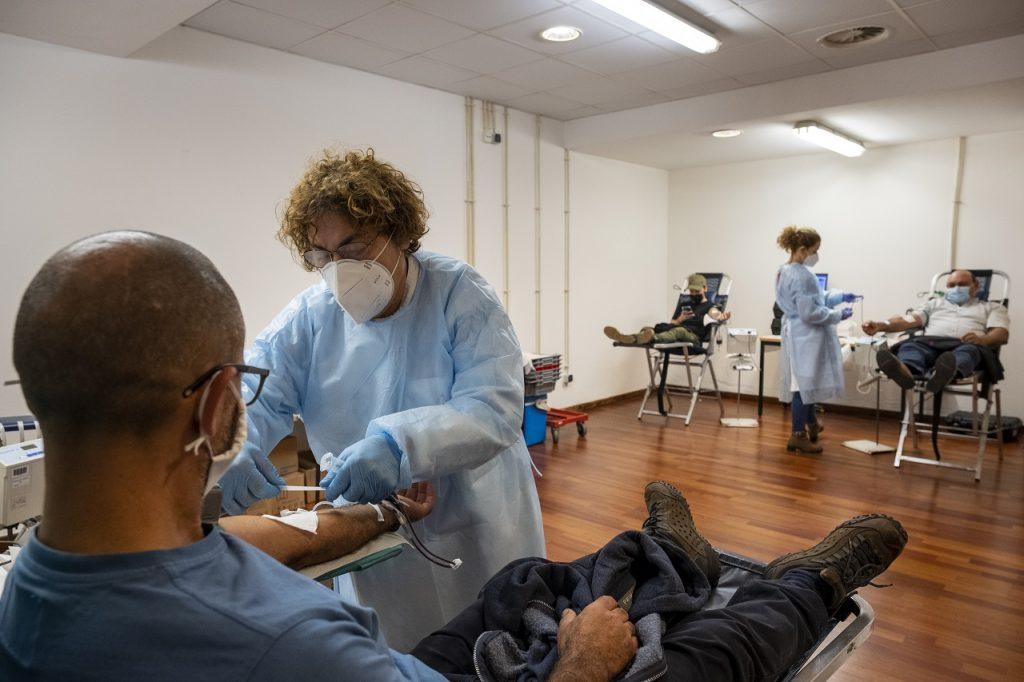 Três pessoas estão sentadas em cadeirões para dar sangue com apoio de duas enfermeiras