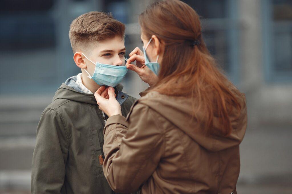 fotografia de uma mãe a colocar uma máscara cirúrgica no filho